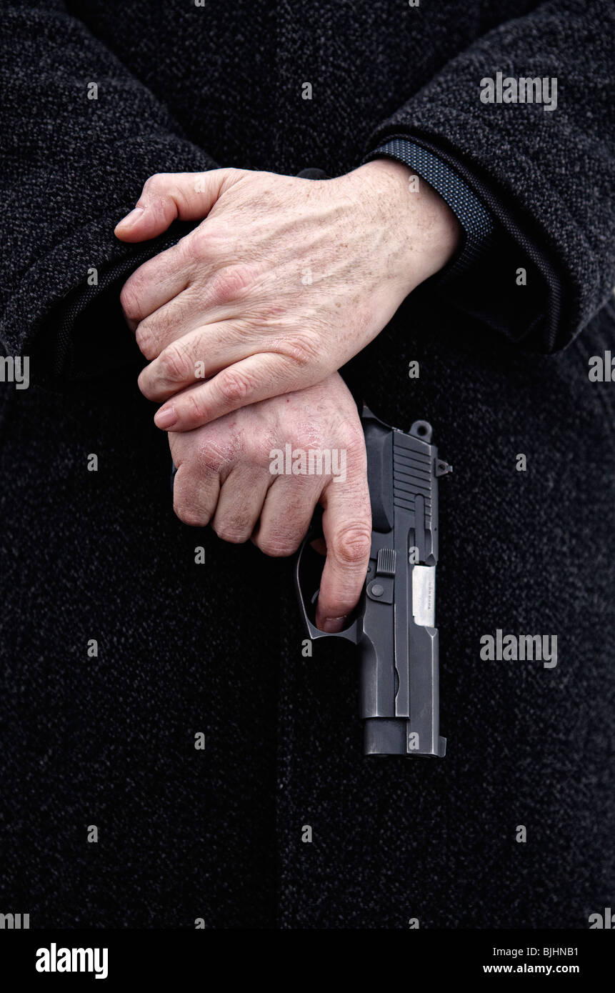 Man holding gun in hands-close-up - Stock Image