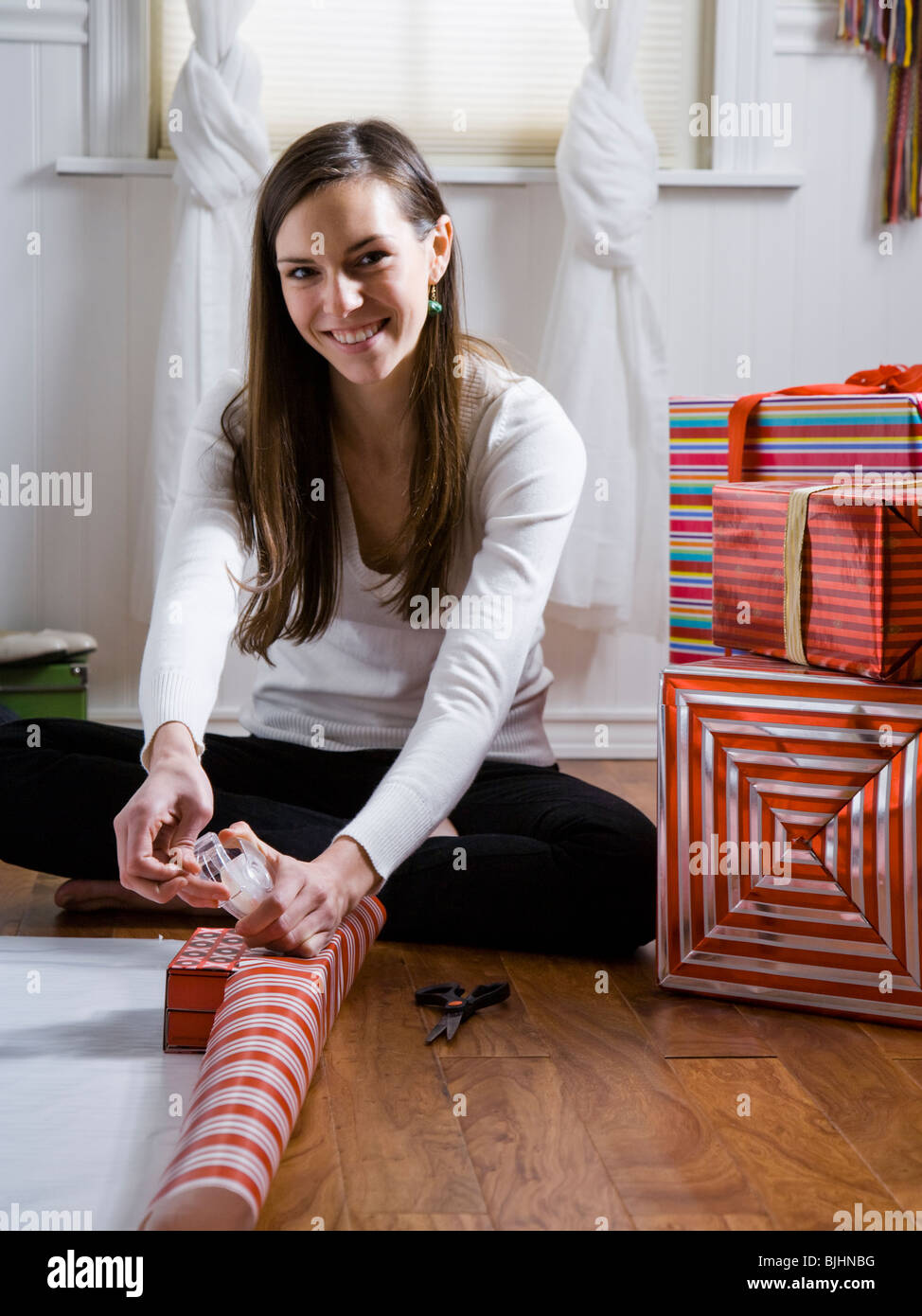 woman sitting on the floor wrapping presents - Stock Image