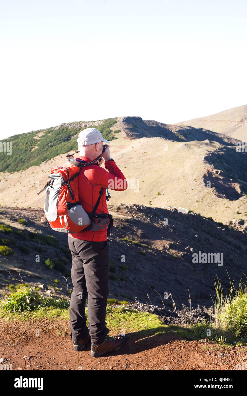 A man photographs the scenery from a hillside during the Madeira Islands Walking Festival. - Stock Image