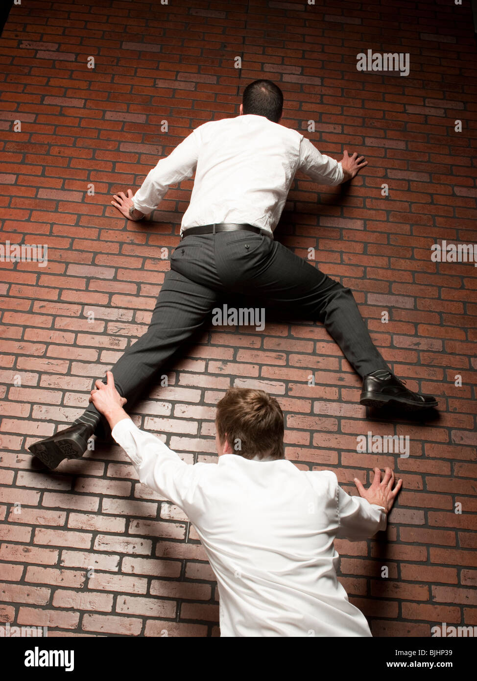 man climbing up a brick wall while another man grabs on to his leg - Stock Image