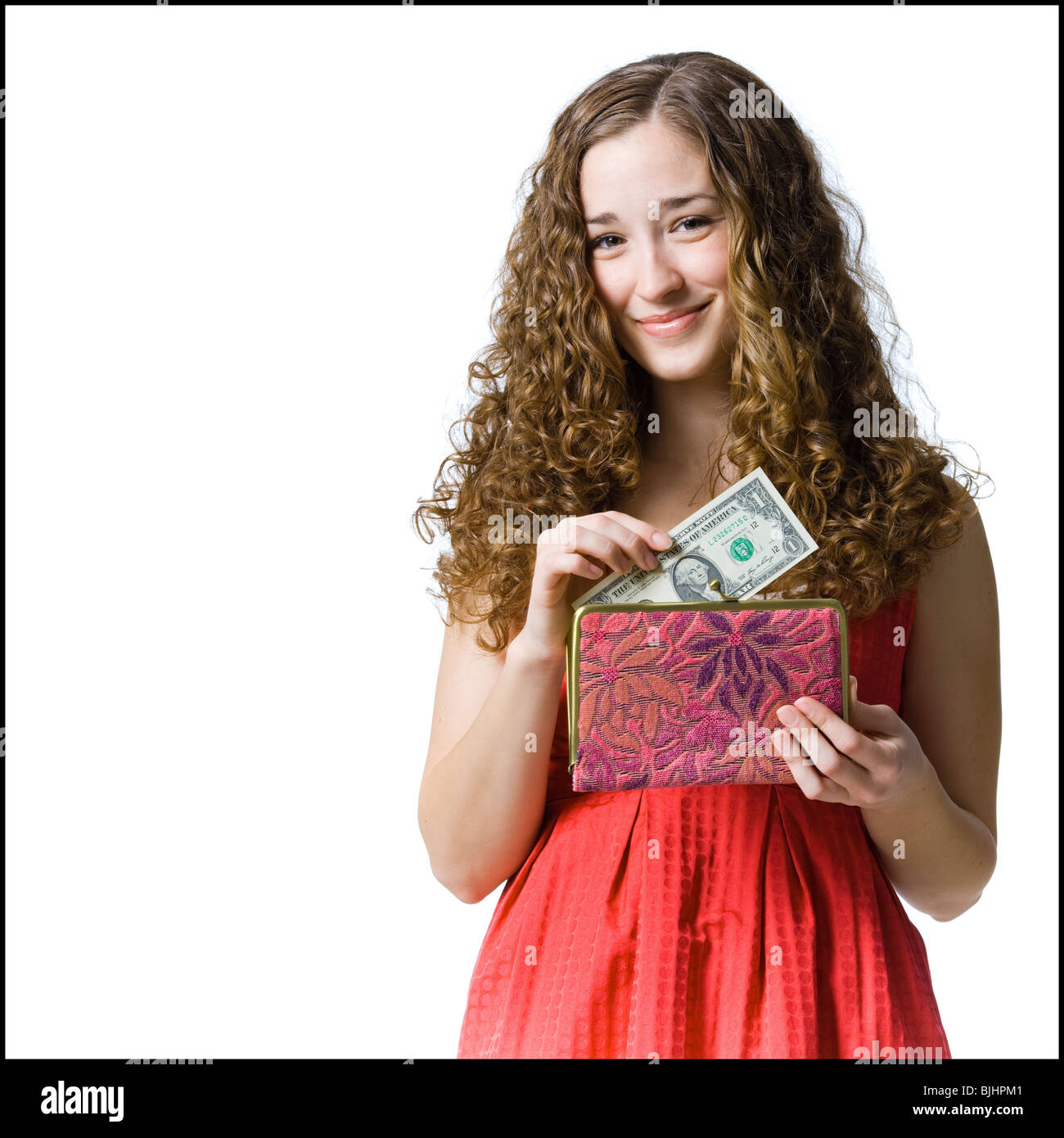 woman putting money in her purse - Stock Image
