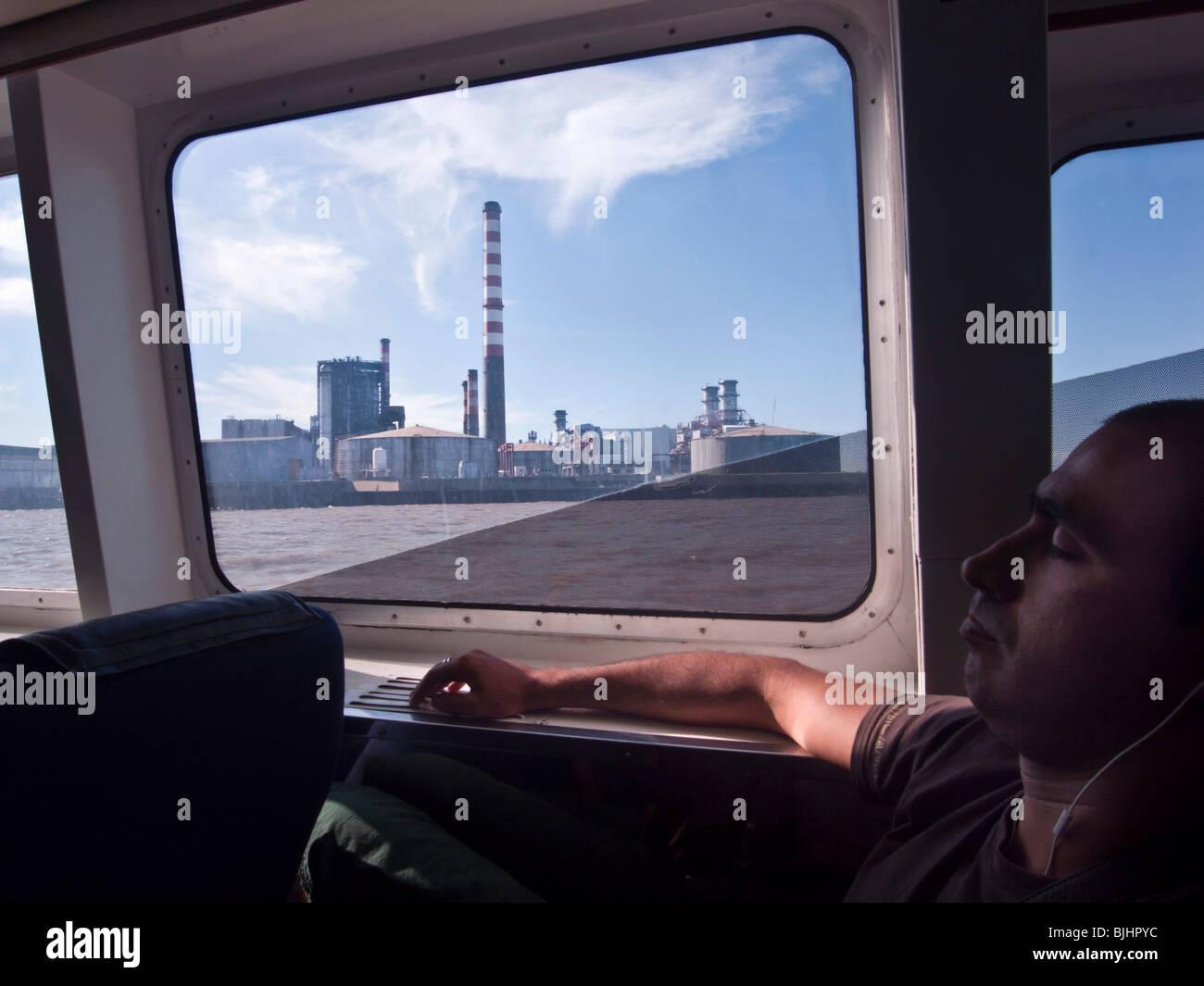 Man taking a nap on the ferry ride from Montevideo, Uruguay to Buenos Aires, Argentina. - Stock Image