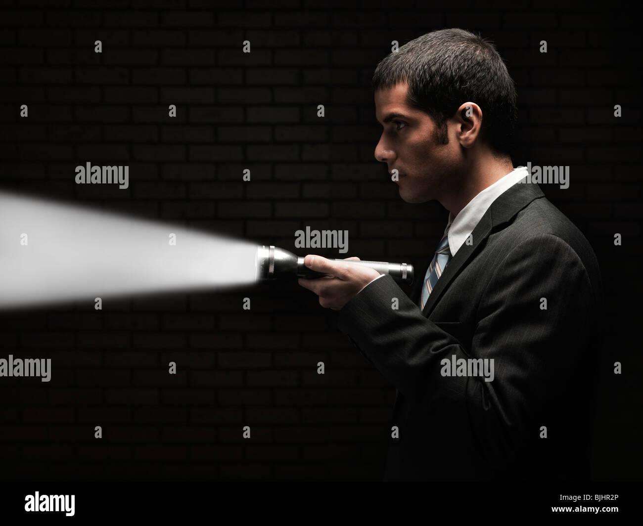businessman holding a flashlight - Stock Image