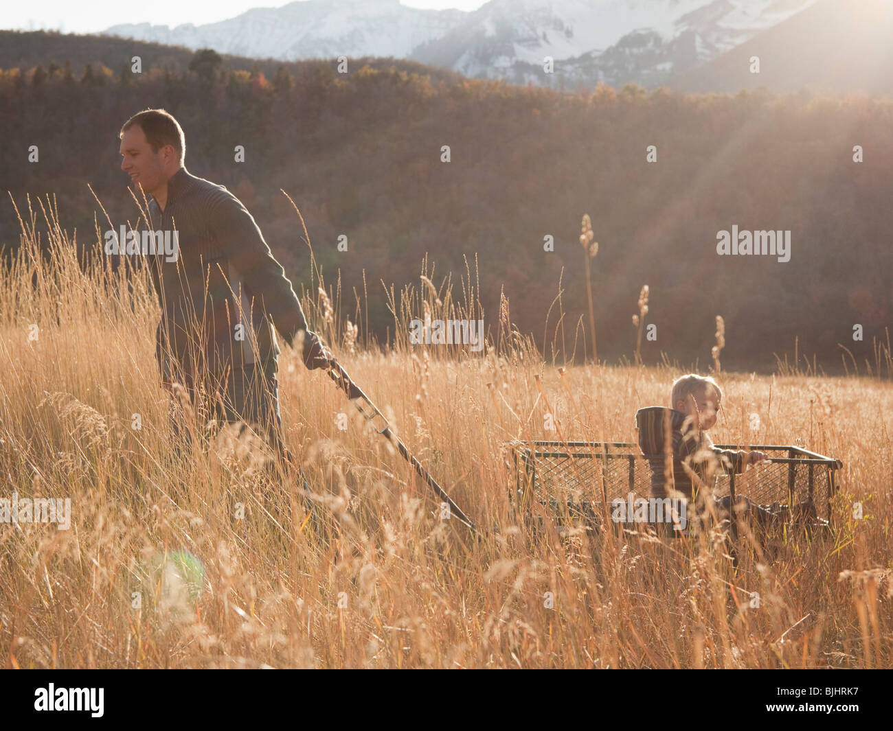 Father pulling son in wagon - Stock Image