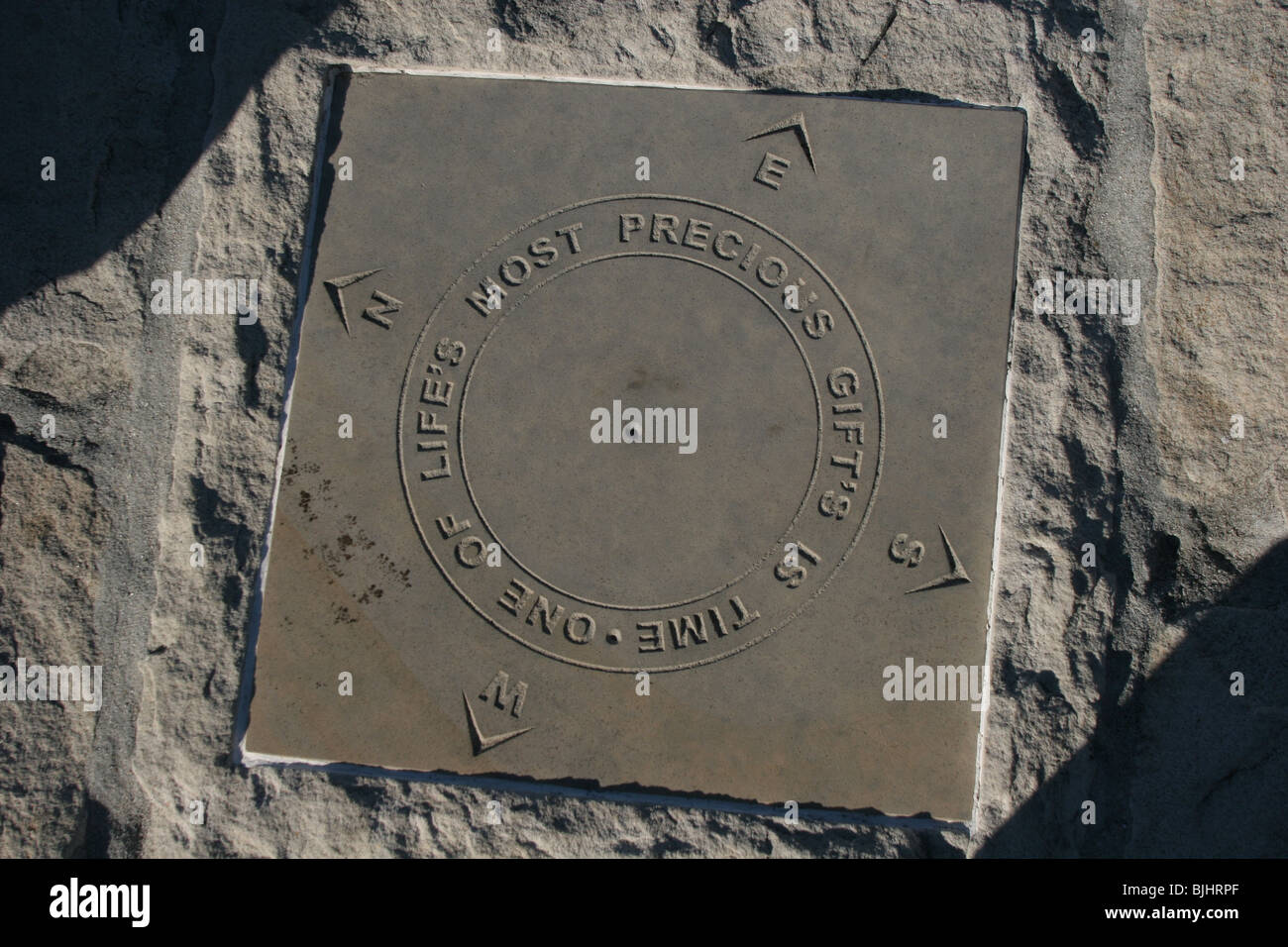 Compass points plaque inscribed 'One of Life's Most Precious Gifts is Time' - Stock Image