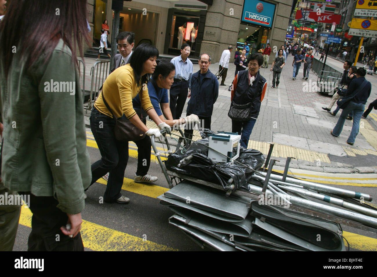 Two women pushing a cart laden with scrap metal through a street in Central district, Hong Kong Island, China - Stock Image