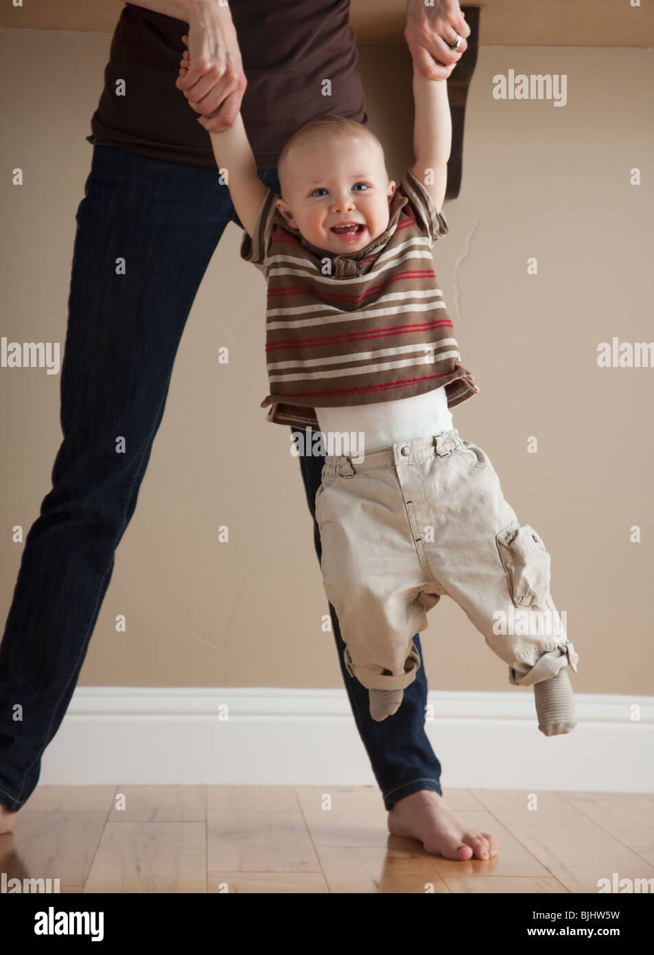 Mother swinging toddler - Stock Image