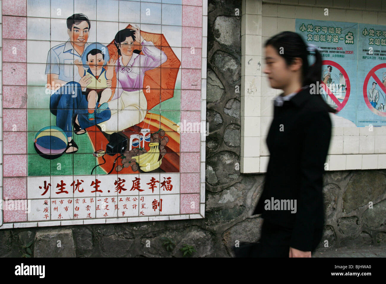 A tiled mural in a Guangzhou street advocates 'happy families', and China's 'one child' policy - Stock Image