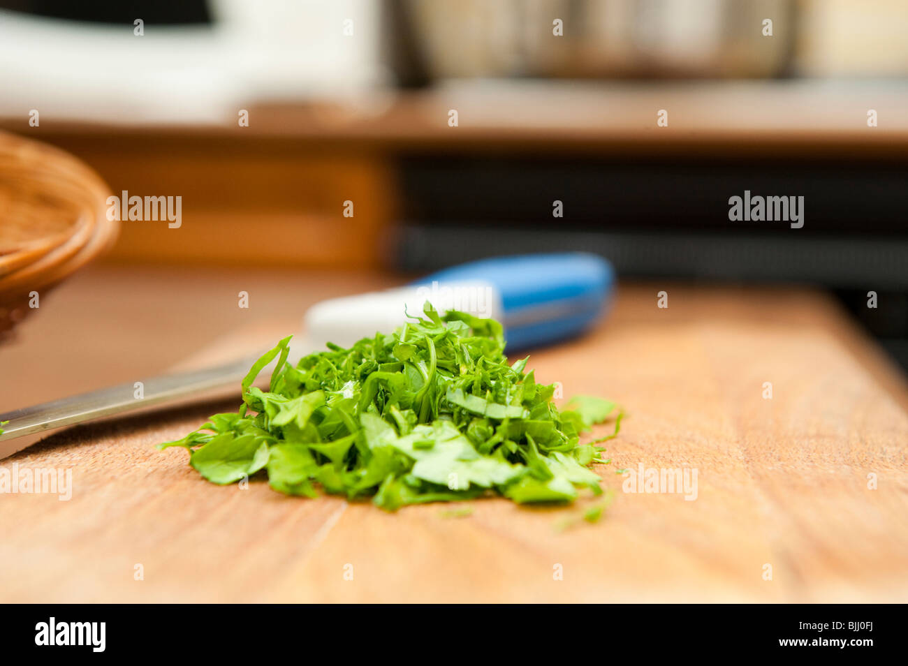 some parsley chopped on a wooden board ready to be used as an ingredient - Stock Image