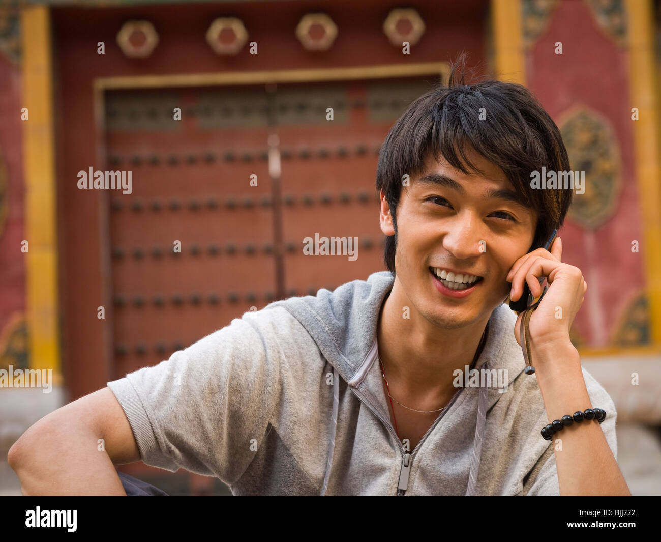 Teenage boy outdoors with cell phone smiling - Stock Image