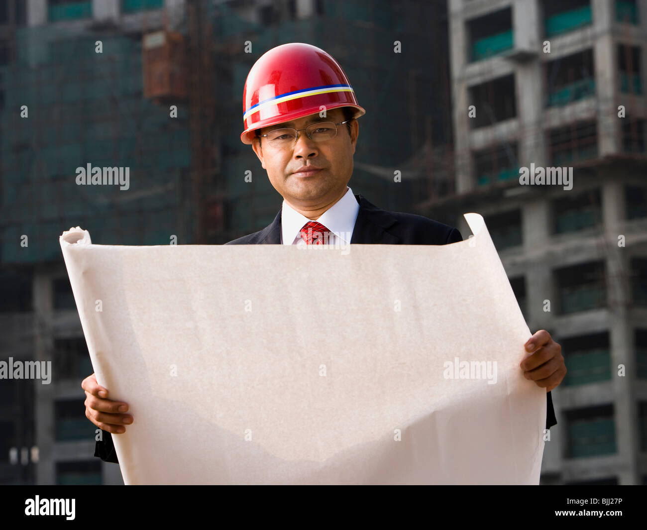 Construction site foreman with blueprints outdoors - Stock Image
