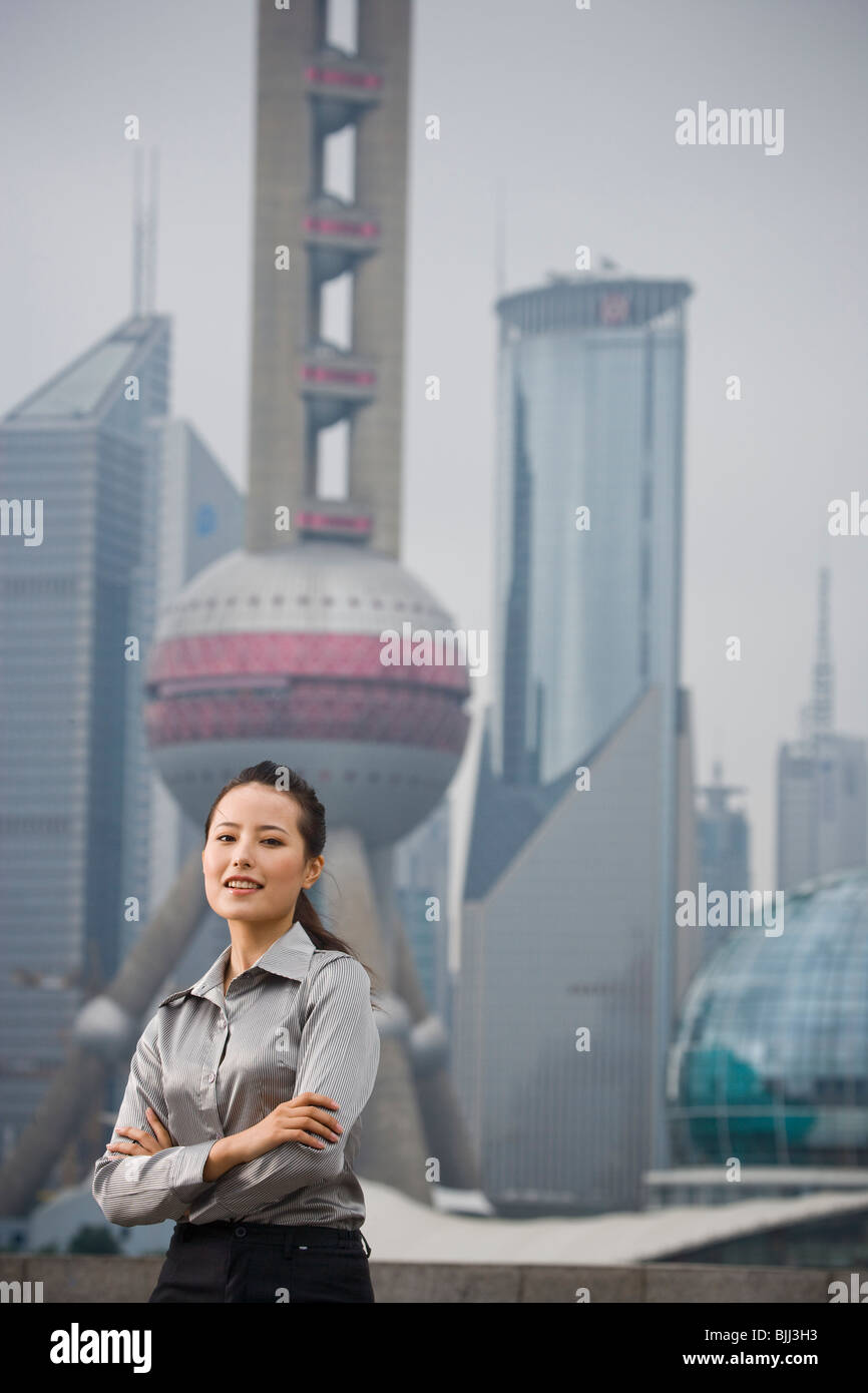 Businesswoman smiling outdoors with arms crossed Stock Photo