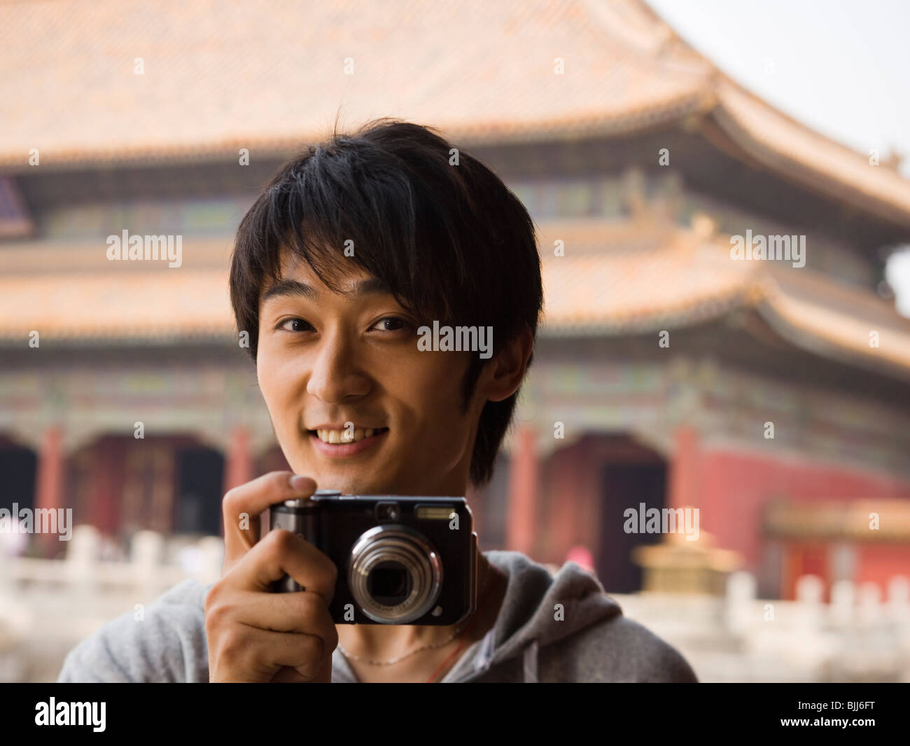 Teenage boy outdoors with digital camera smiling - Stock Image