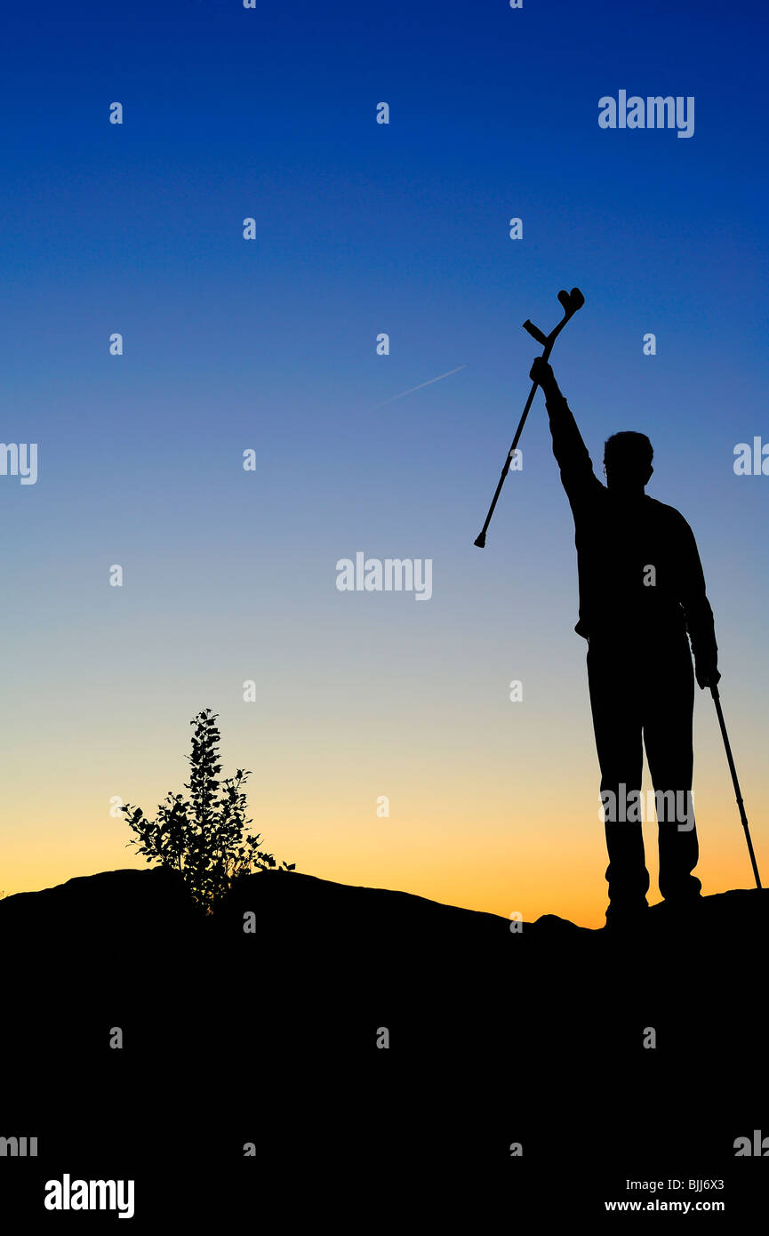 A disabled man stands on a ridge, greeting the sunrise. Contrail of passing jet in the sky (can be cloned out if - Stock Image