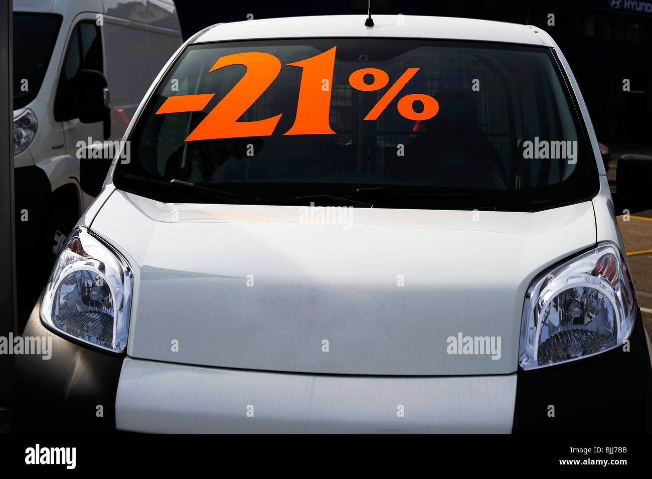 A new car displayed outside a showroom showing a 21% reduction on the price. - Stock Image