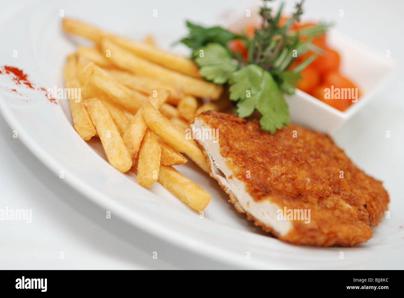 Fried chicken fillet with chips and carrots served for lunch in restaurant - Stock Image