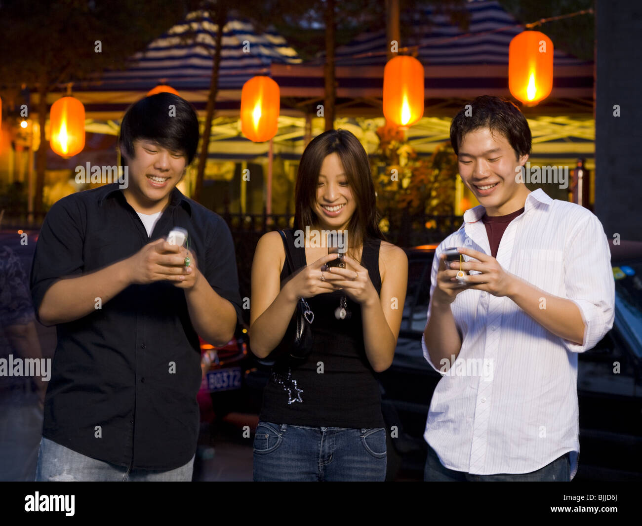 Three people with cell phones outdoors at night smiling - Stock Image