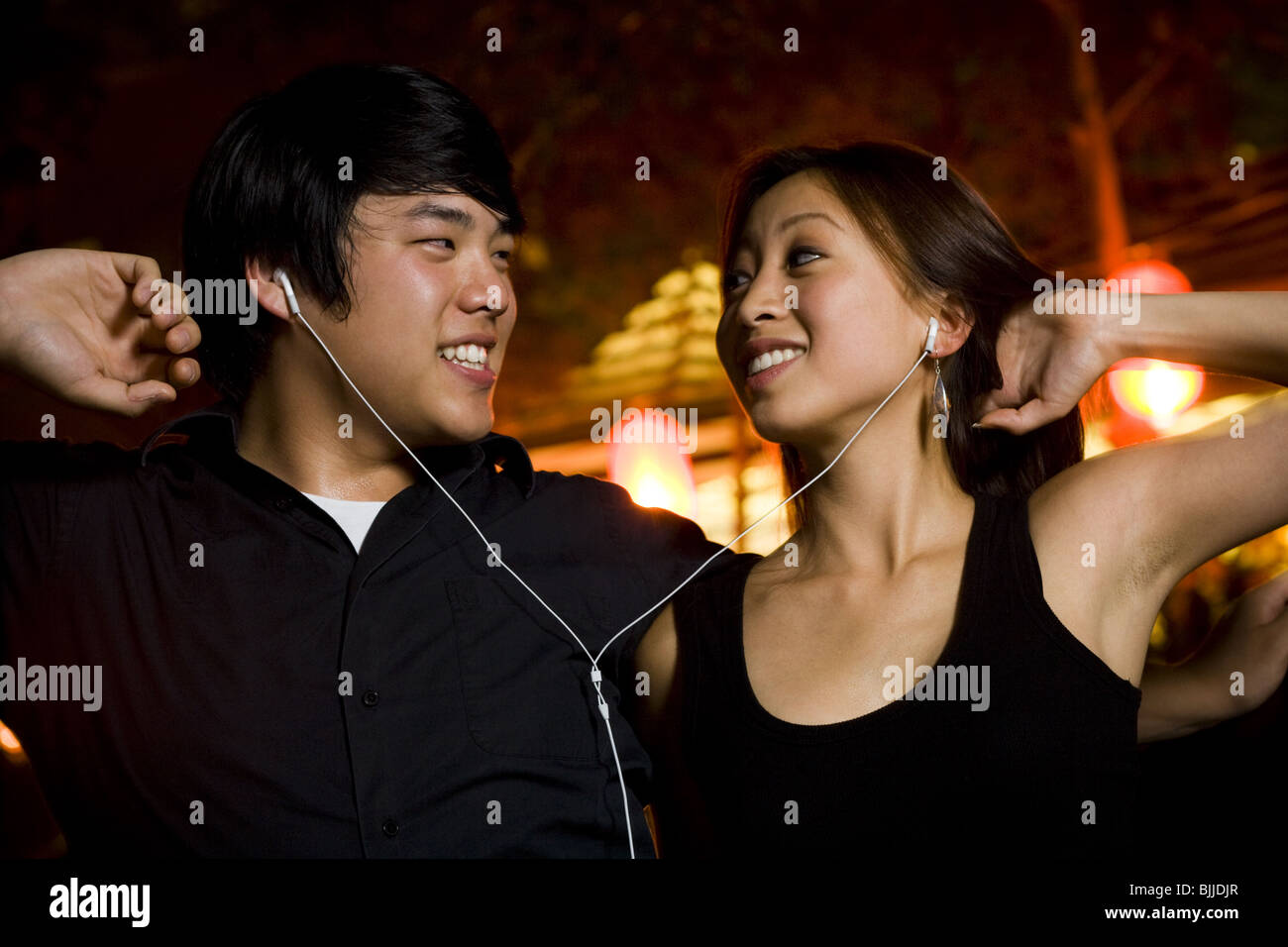 Couple listening to mp3 player outdoors dancing and smiling - Stock Image