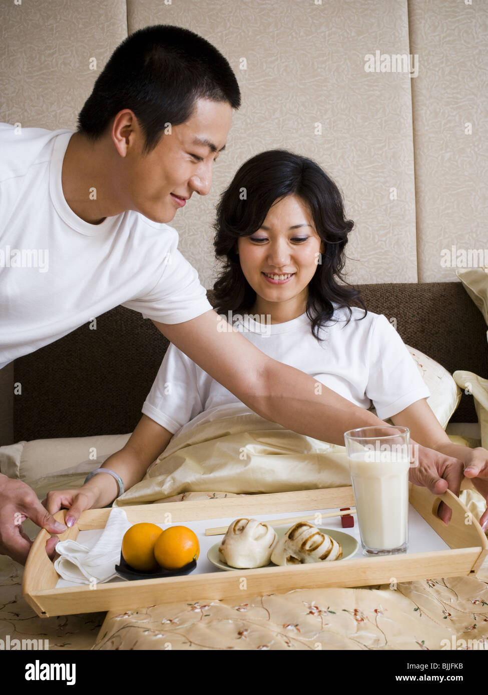 Man bringing woman breakfast in bed - Stock Image