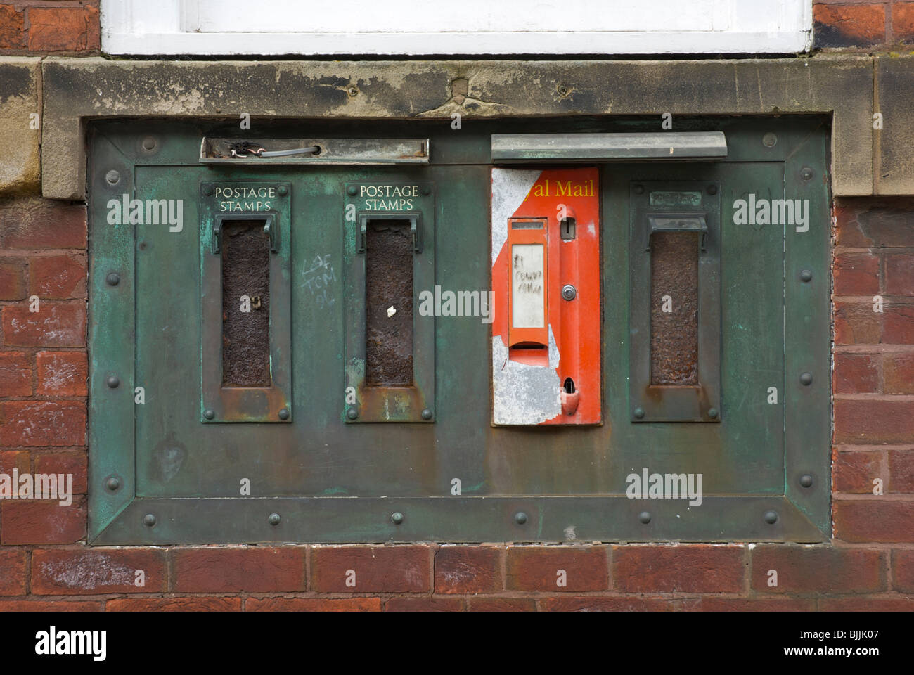 Old stamp dispensing machine in wall of Post Office, Maryport, West Cumbria, England UK - Stock Image