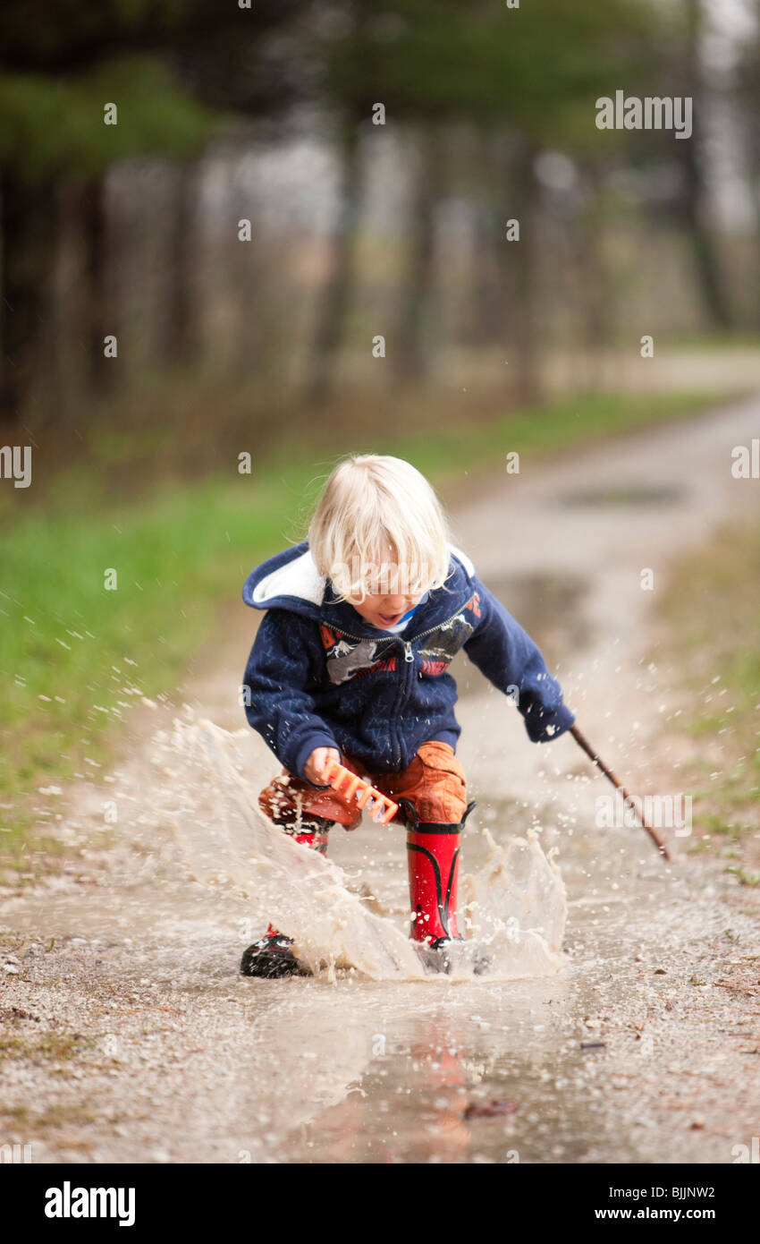 Young boy making a splash in a puddle of water. - Stock Image