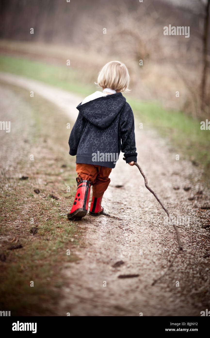 Young boy wearing rain boots walks through a puddle of water. Stock Photo