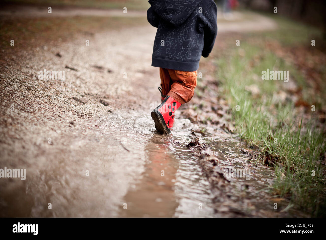 Young boy wearing rain boots walks through a puddle of water. - Stock Image