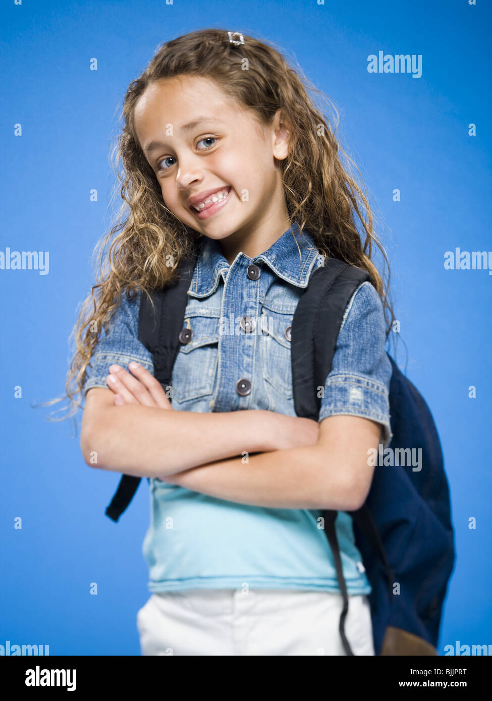 Smiling girl with arms crossed and backpack - Stock Image