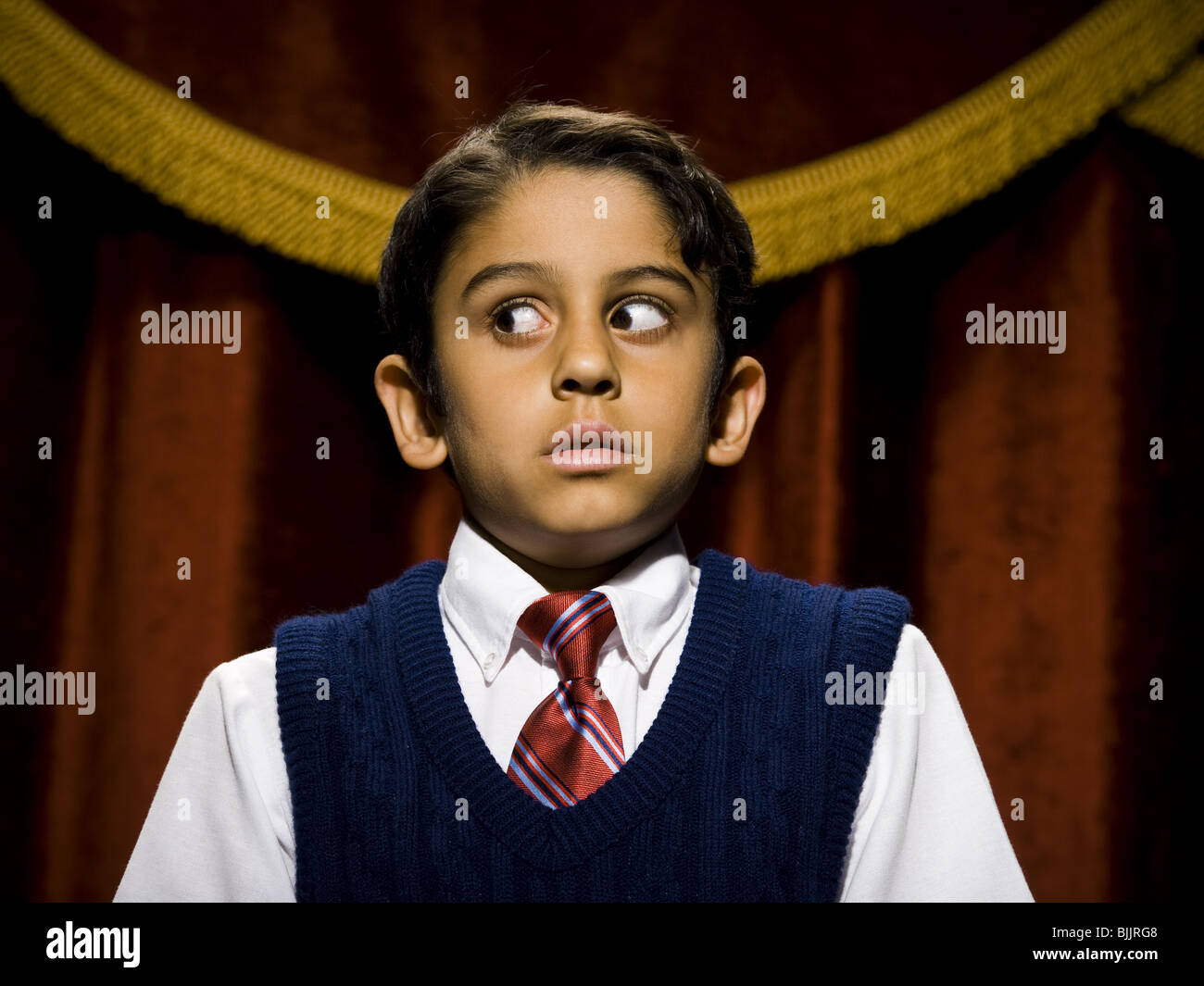 Boy standing on stage with microphone and big eyes - Stock Image