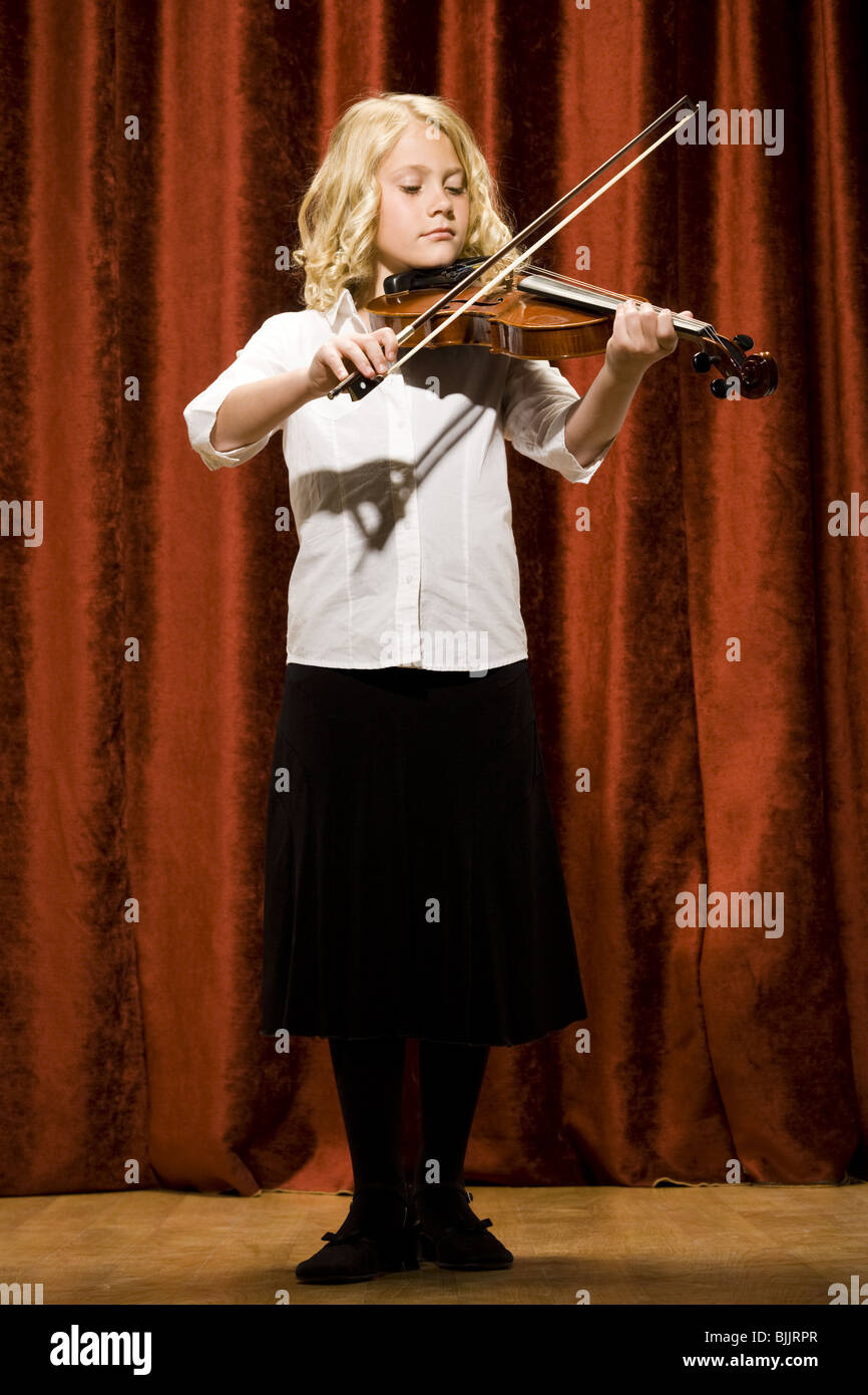 Girl playing violin on stage - Stock Image