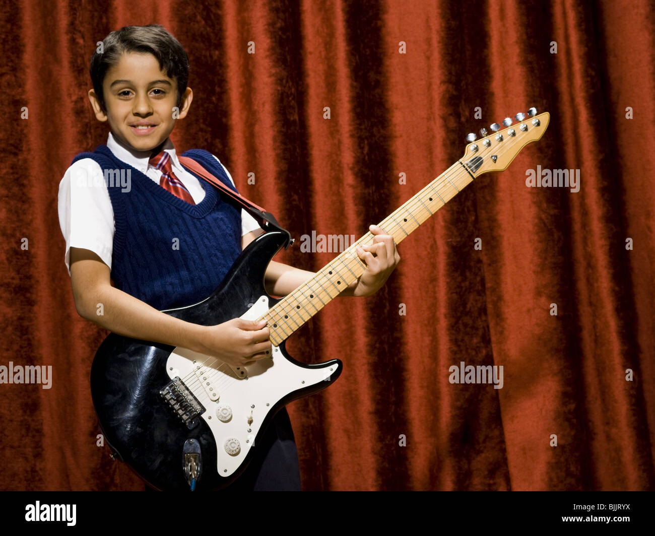 Boy on stage playing electric guitar - Stock Image