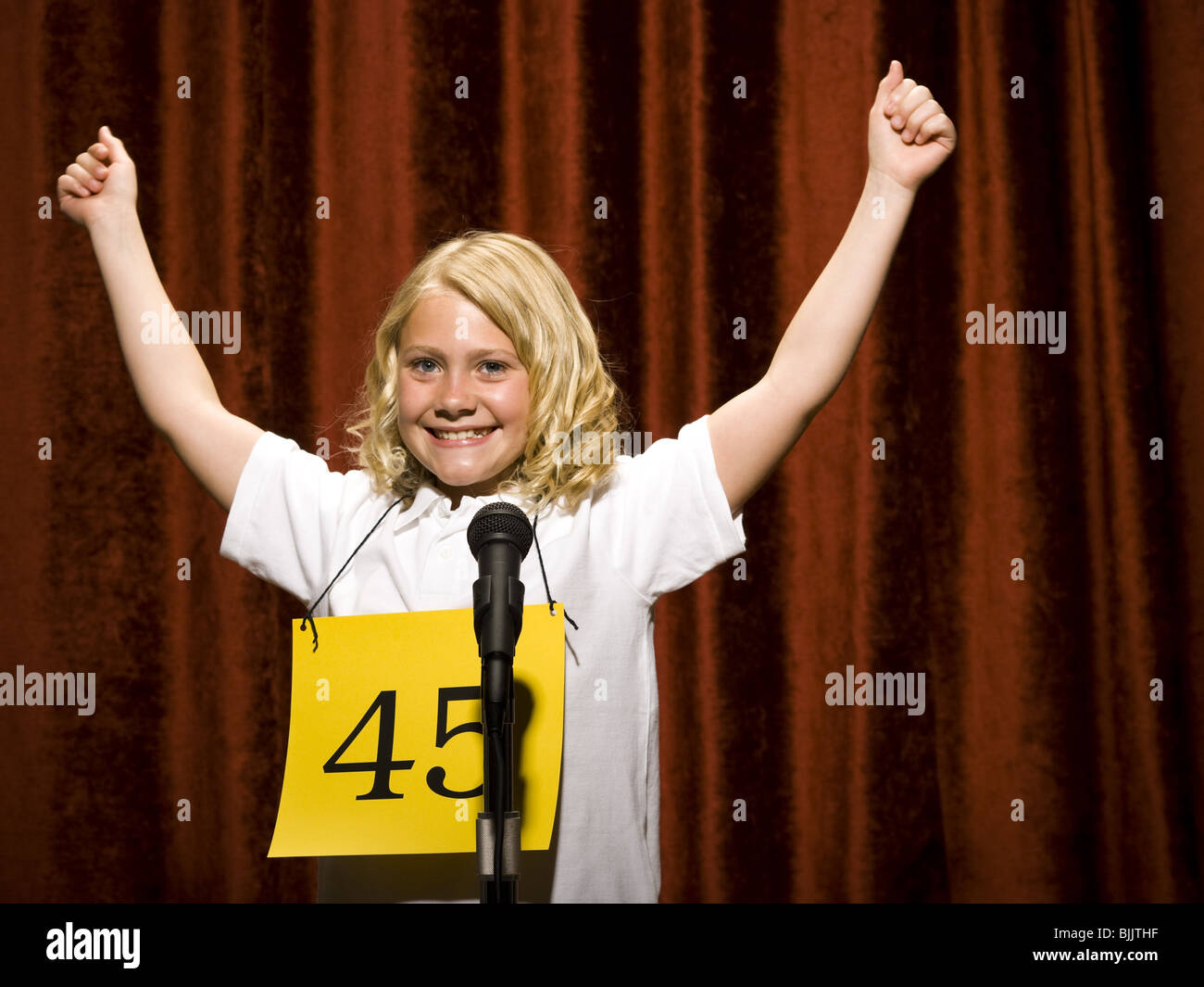 Girl contestant standing at microphone cheering - Stock Image