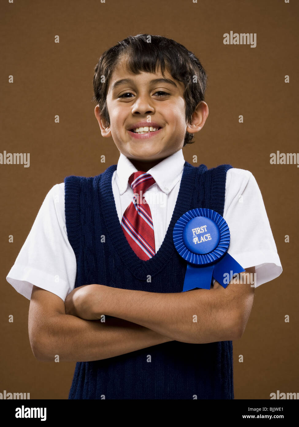 Boy with first place ribbon and arms crossed smiling - Stock Image