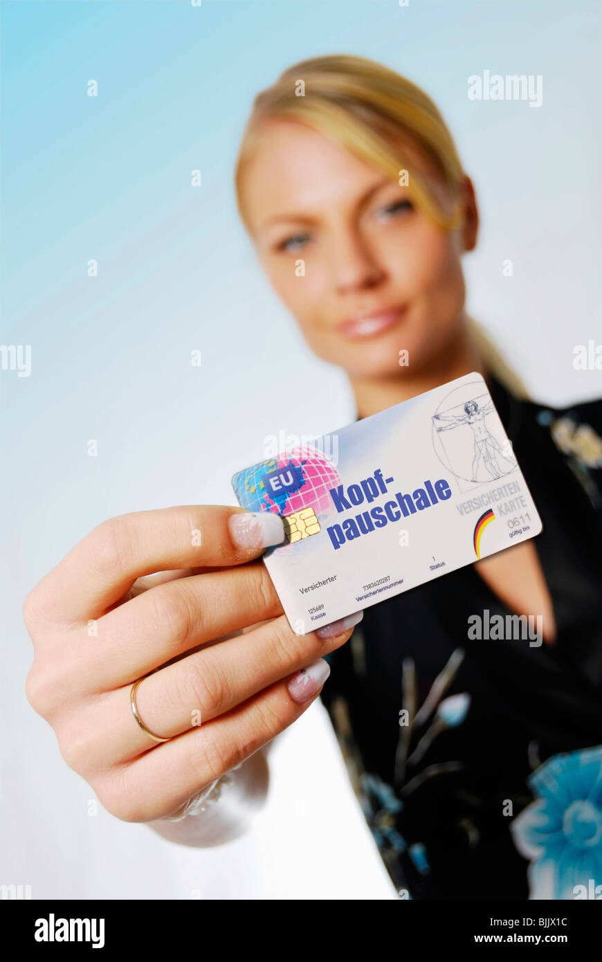 Young woman holding insurance card, Kopfpauschale, capitation fee, written on it - Stock Image