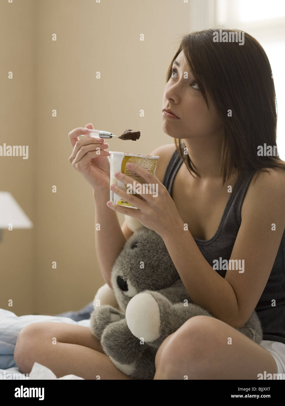 Woman eating chocolate ice cream in bed with stuffed animal - Stock Image