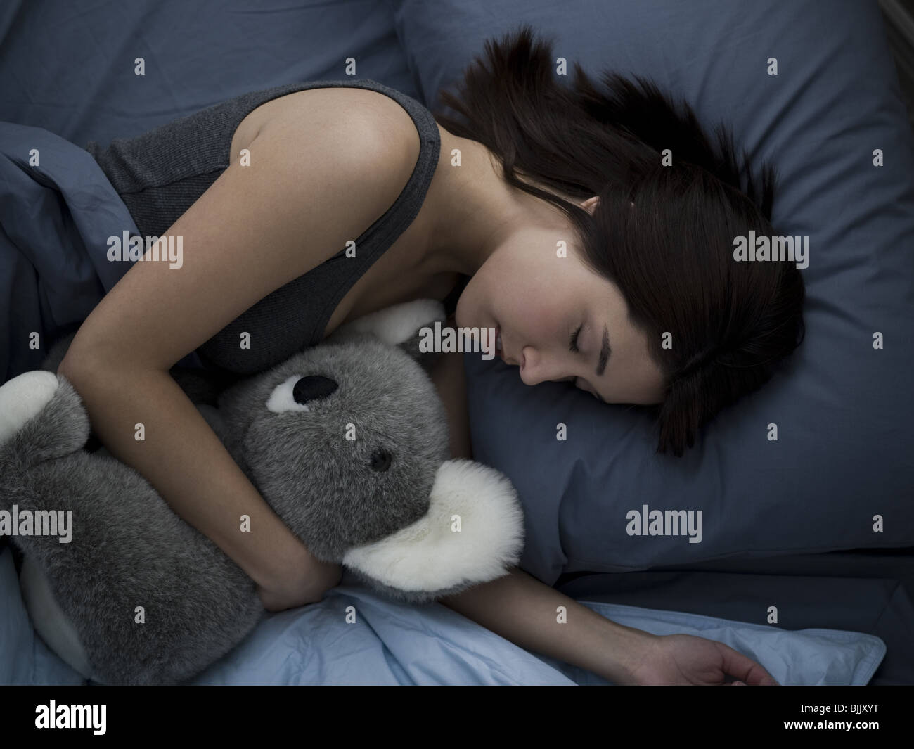 Woman sleeping in bed with stuffed animal - Stock Image