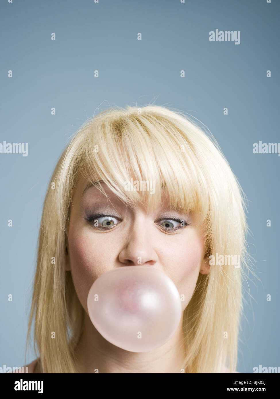Woman blowing bubbles with chewing gum - Stock Image