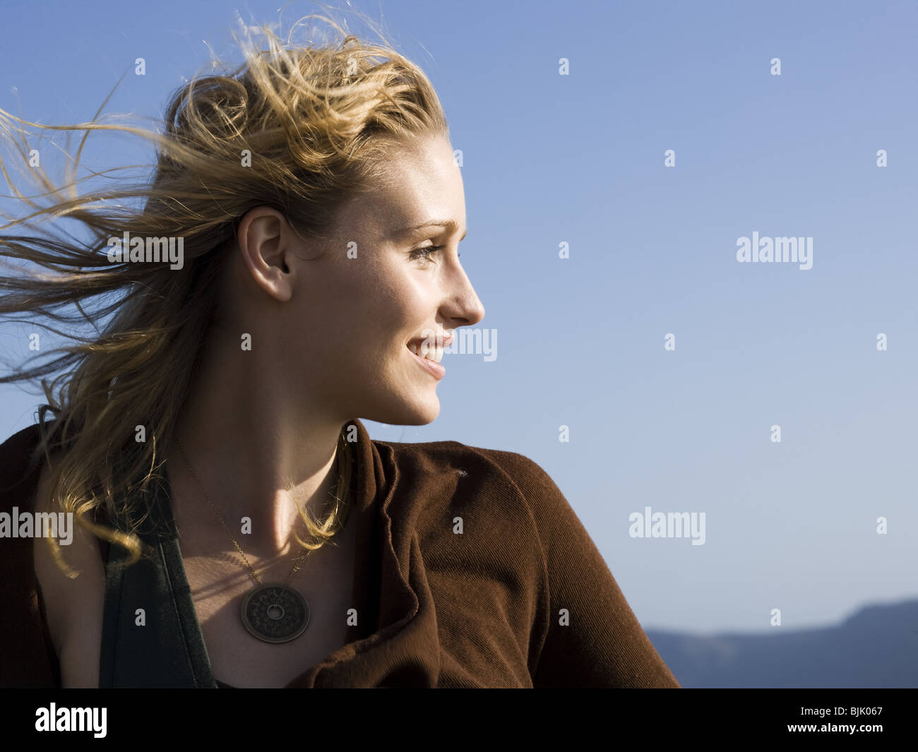 Closeup of woman smiling outdoors with blue sky - Stock Image