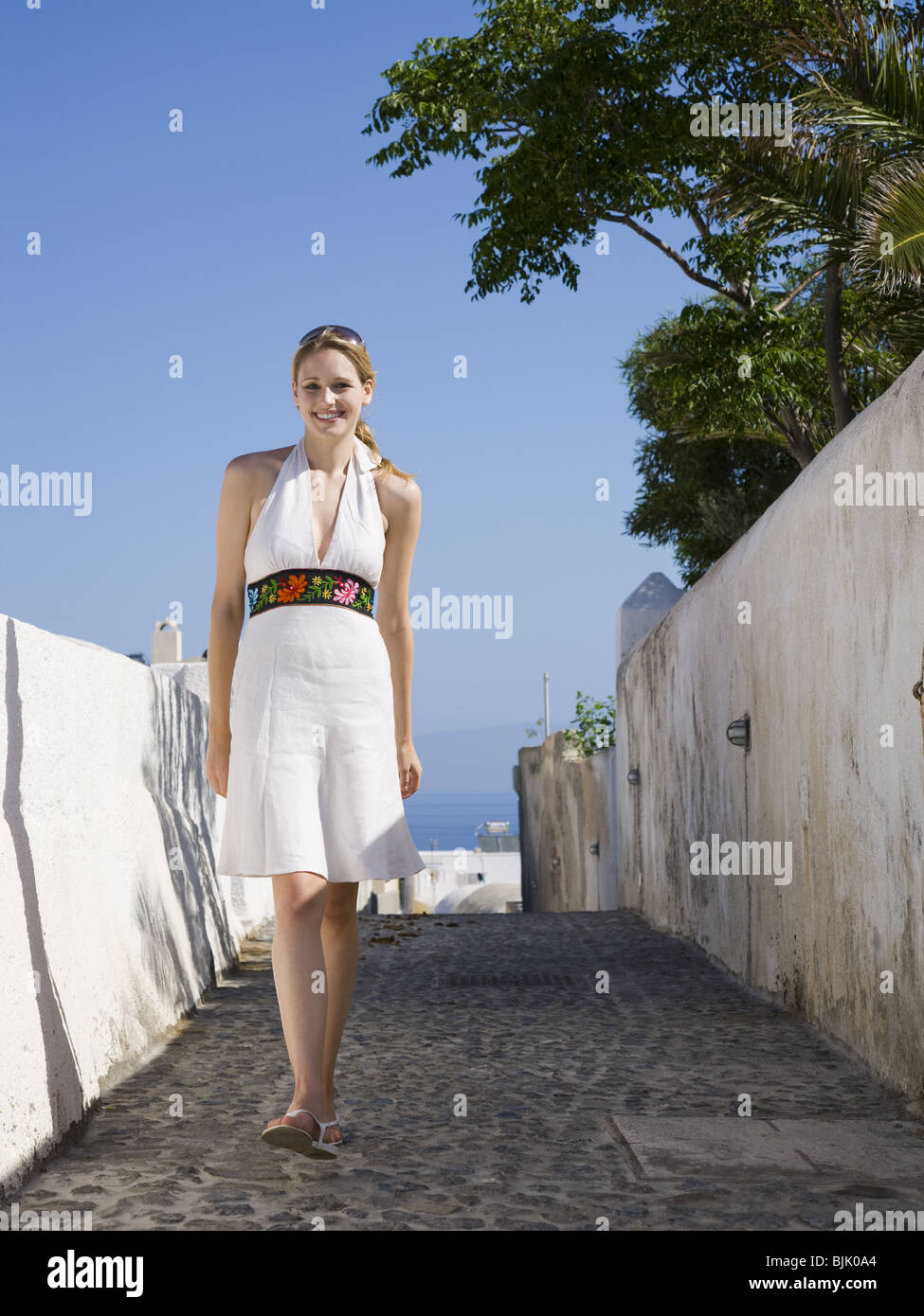 Woman leaning on wall and smiling outdoors - Stock Image