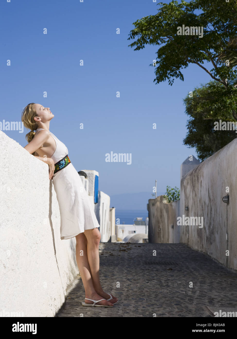 Woman leaning on wall outdoors smiling - Stock Image