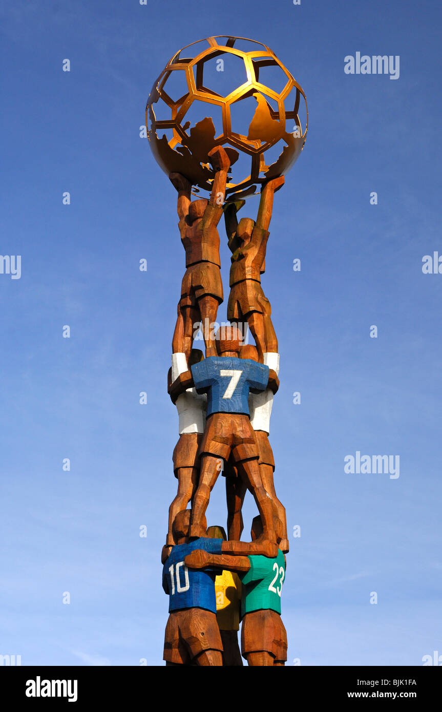 Football monument in the form of a pyramid of football players, holding a globe in front of the Home of FIFA, headquarters - Stock Image