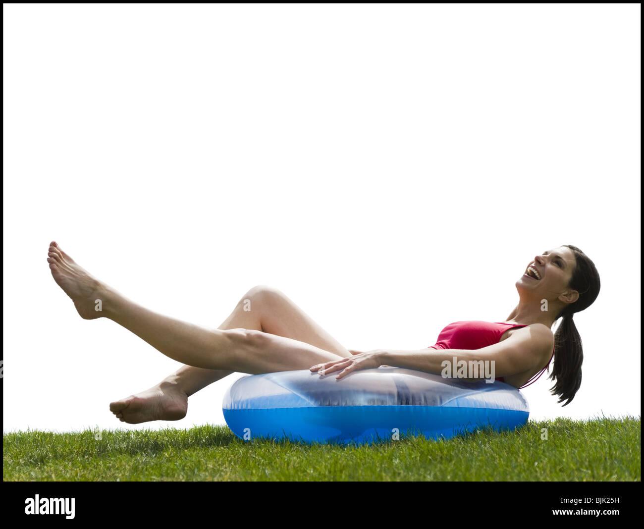 Woman in bikini lying in swimming ring on grass smiling Stock Photo