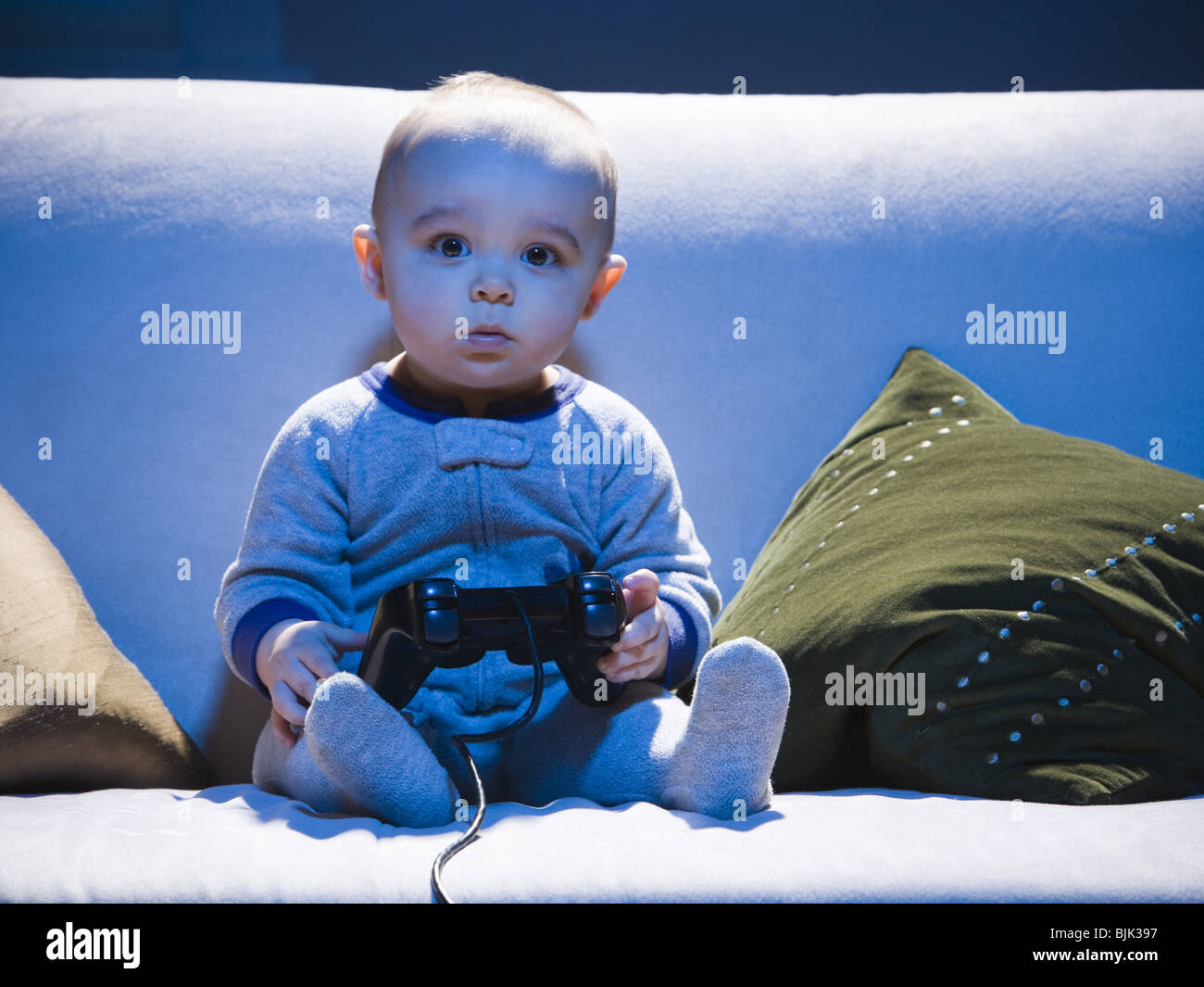 Baby on sofa with video game controller - Stock Image