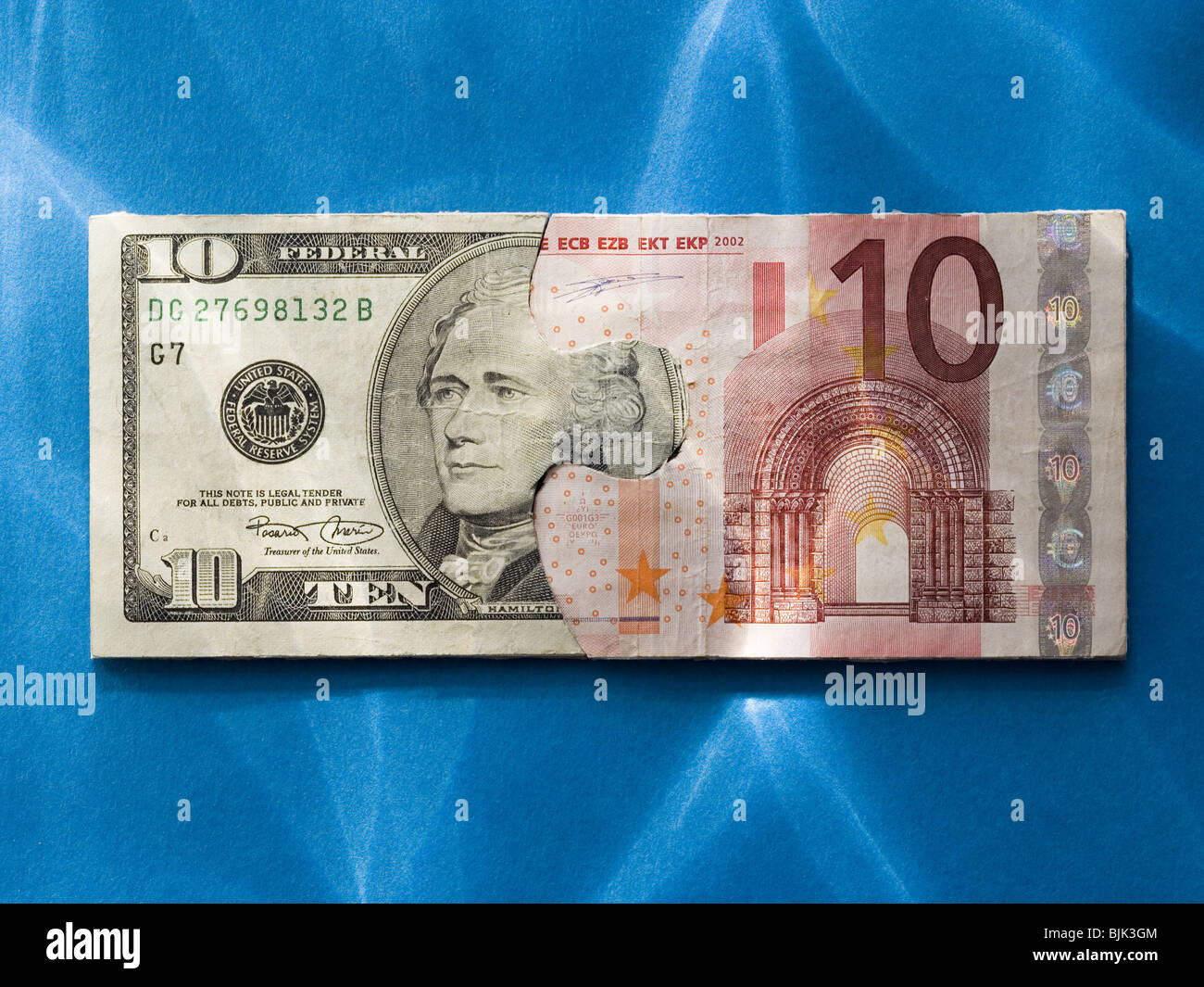 Puzzle pieces of ten dollar bill and ten euro banknote - Stock Image