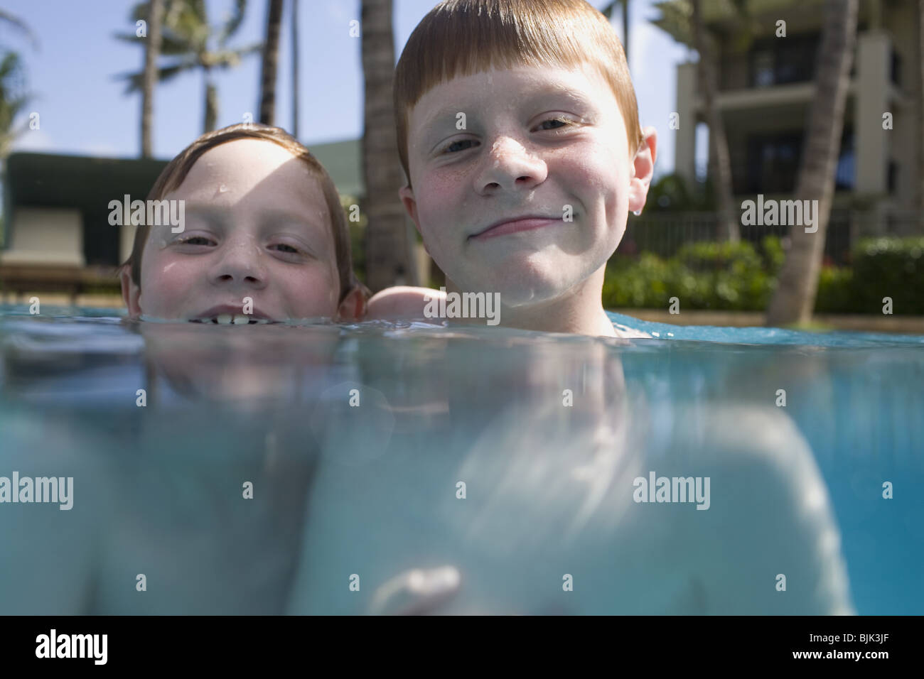 Two boys in outdoor pool smiling - Stock Image