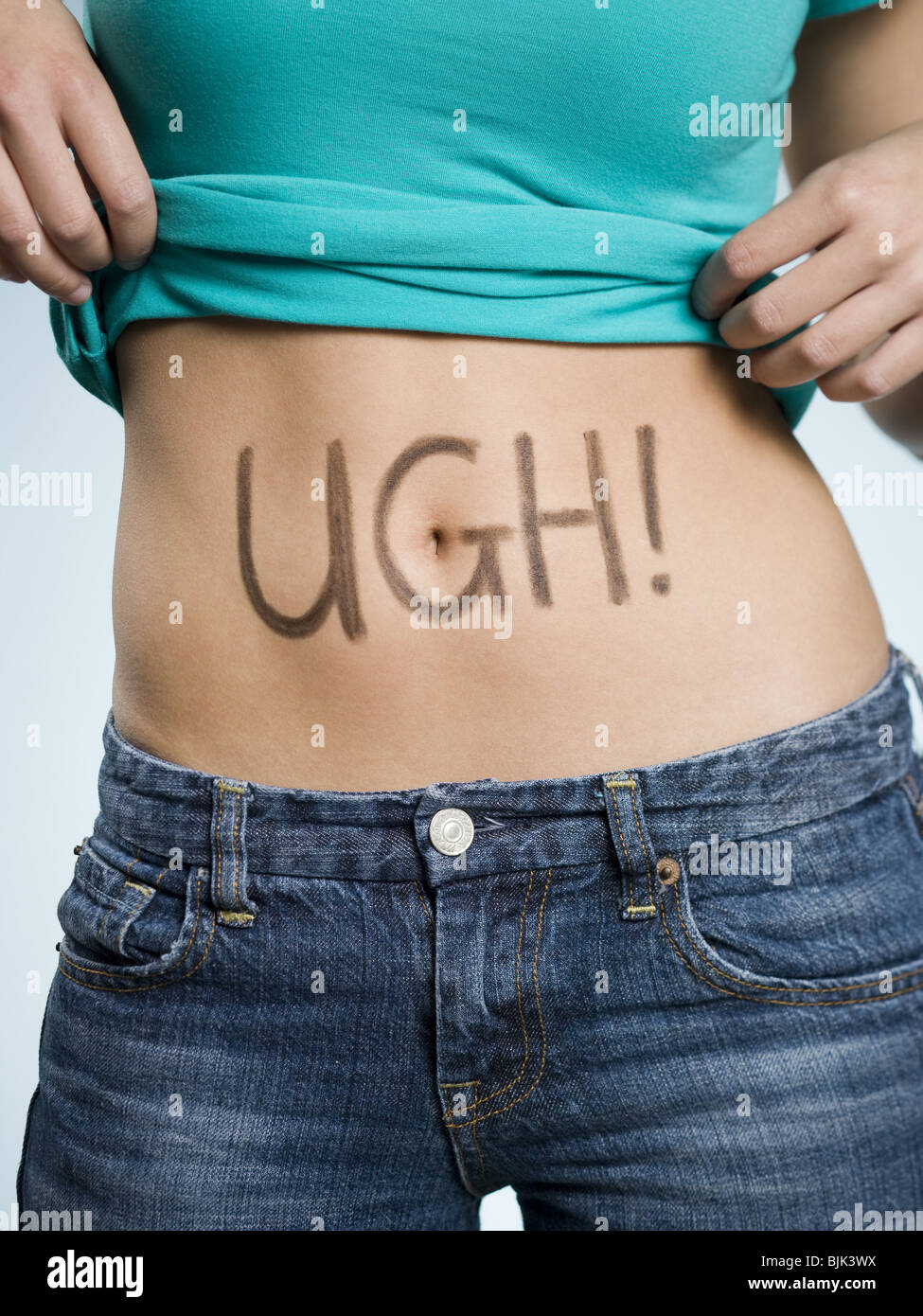 Female Abdomen with UGH! written on it Stock Photo