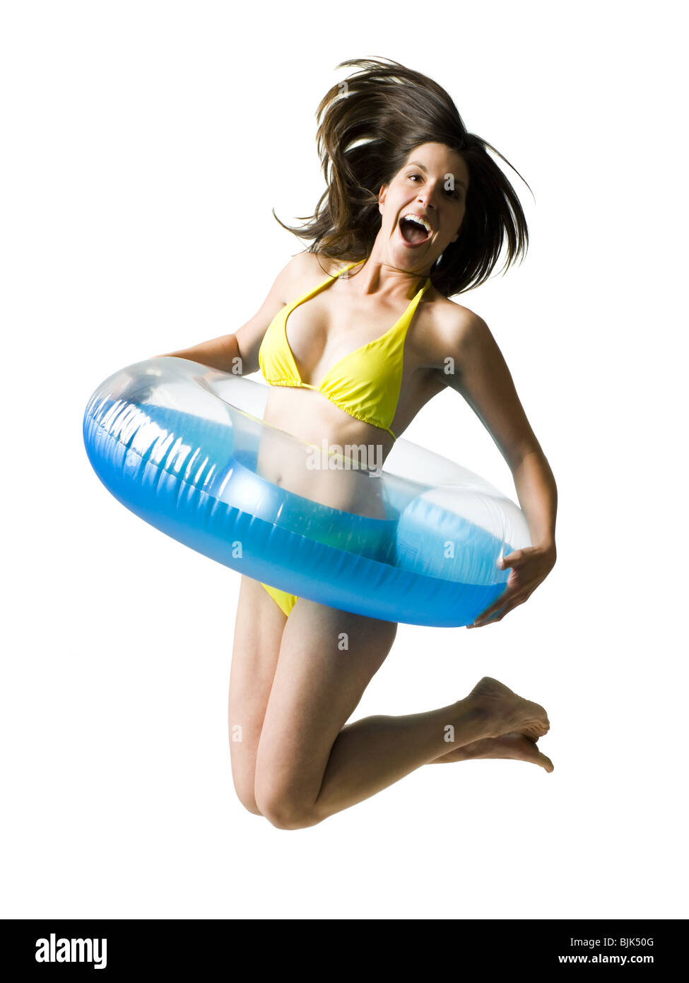 Woman in bikini with swimming ring around waist jumping and smiling Stock Photo
