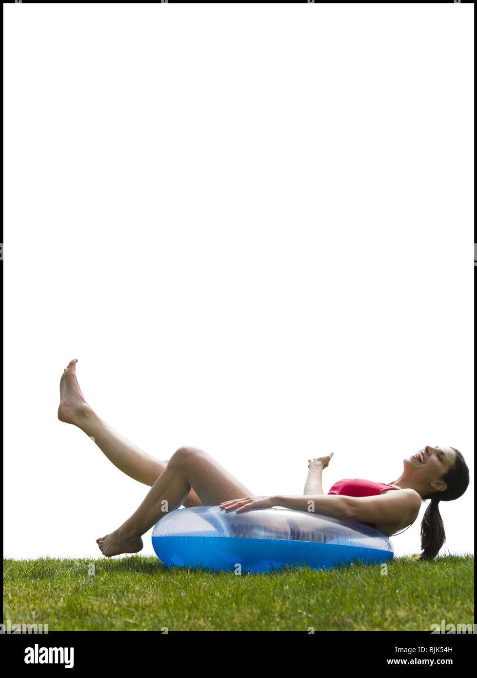 Woman in bikini lying in swimming ring laughing Stock Photo