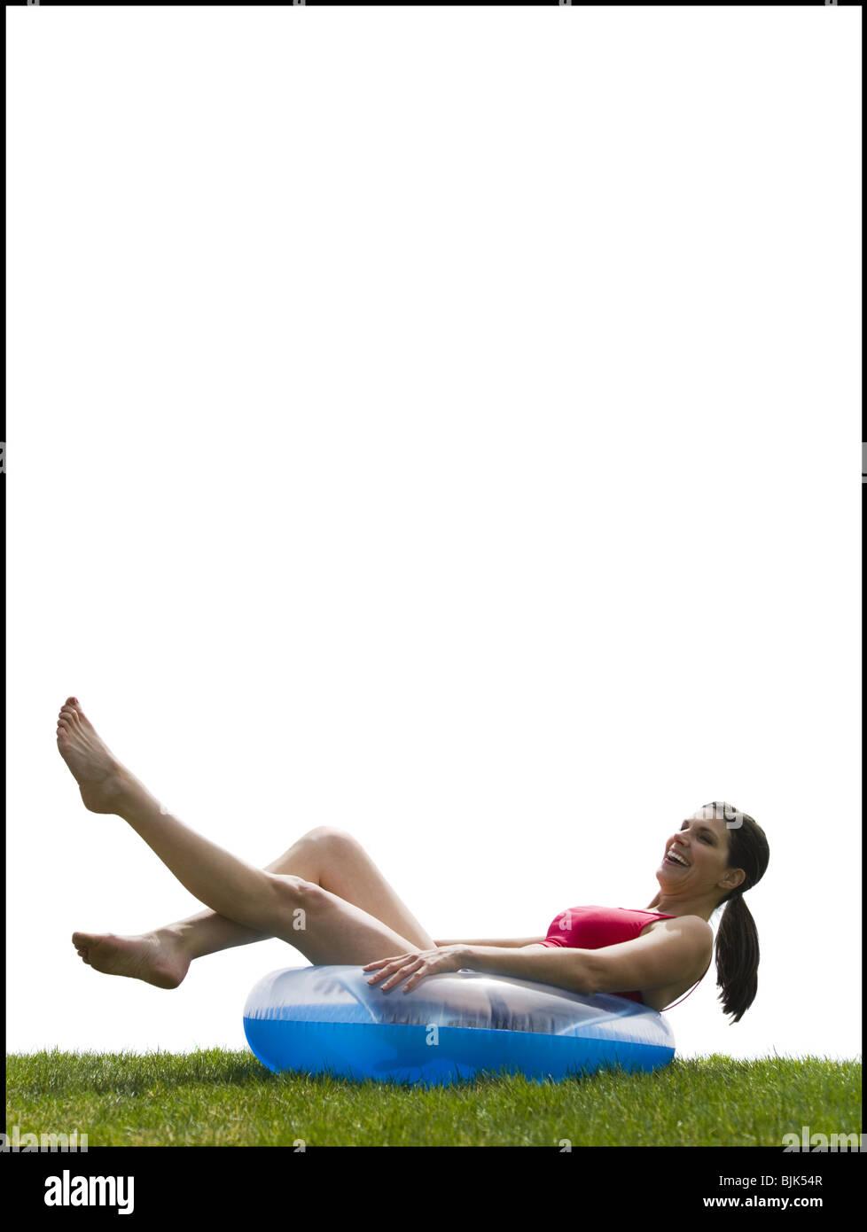 Woman in bikini lying in swimming ring laughing Stock Photo