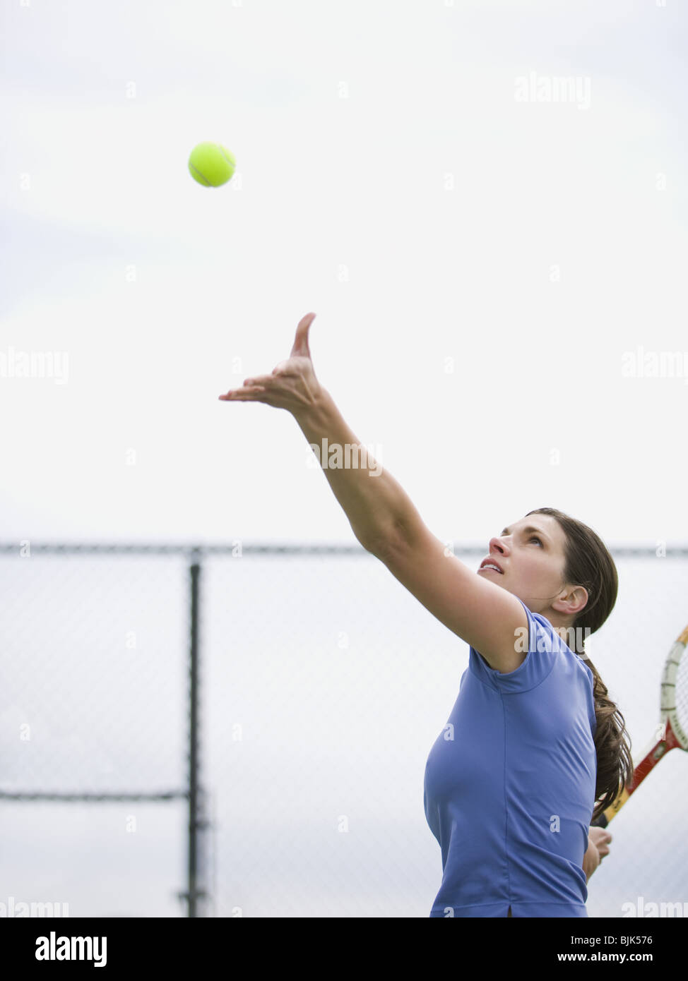 Woman tossing tennis ball in air to serve - Stock Image